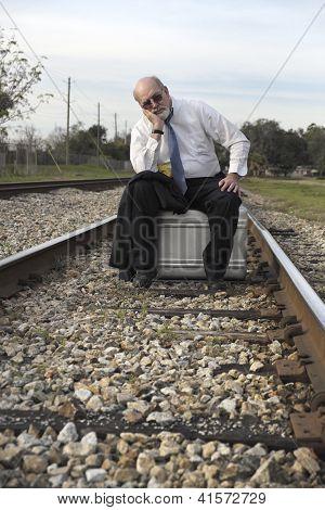Unemployed Senior Businessman Sits On Suitcase On Railroad Train Tracks