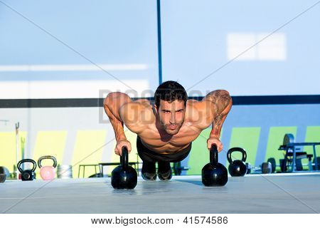 Gym man push-up strength pushup exercise with Kettlebell in a workout
