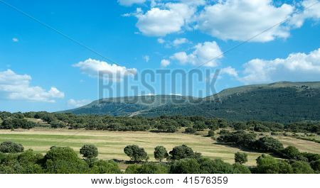 Spanish landscape with plowed filds and hills at the background