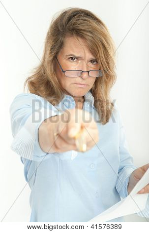 Woman with severe expression, holding a document and pointing at the camera