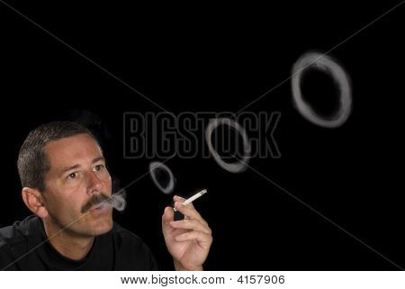Man Smoking And Blowing Smoke Rings
