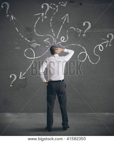Businessman Looking At Arrows Pointed In Different Directions