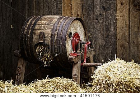 Vintage barrel-type butter churn filled with straw, wooden background