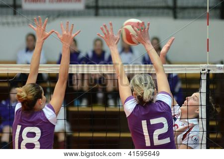 KAPOSVAR, HUNGARY - JANUARY 27: Zsanett Pinter (in white) in action at the Hungarian I. League volleyball game Kaposvar (white) vs Ujpest (purple), January 27, 2013 in Kaposvar, Hungary.