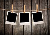stock photo of clotheslines  - Three blank instant photos hanging on the clothesline - JPG