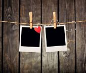 stock photo of clotheslines  - Blank instant photos and small red paper heart hanging on the clothesline - JPG