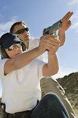 stock photo of handgun  - Trainer helping young woman to aim with handgun at combat training - JPG
