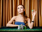 stock photo of roulette table  - Portrait of the female gambler at the roulette table holding chip in the hand - JPG
