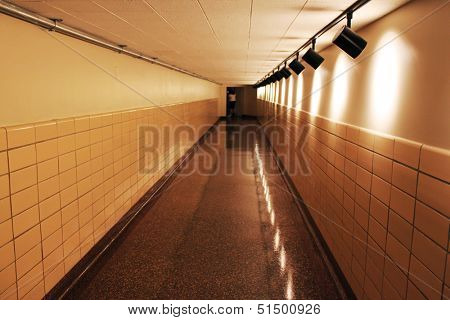 A dark underground tunnel connecting two buildings