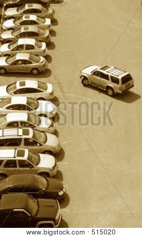 Lone Car Staying Or Leaving A Row Of Parked Cars In A Parking Lot