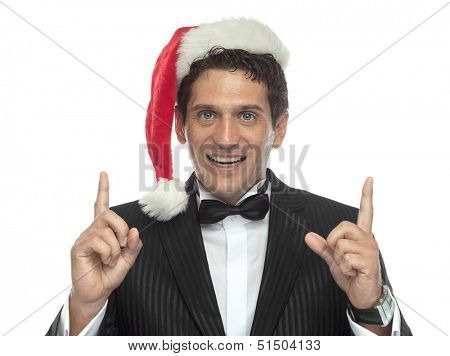 young handsome caucasian man in black dinner jacket looking at camera smiling santa's hat finger hand