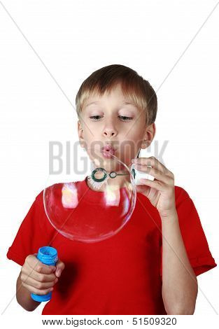 Beautiful blond boy in a bright red t-shirt blowing soap bubbles (isolated on white background)