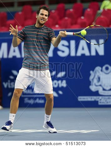 KUALA LUMPUR - SEPTEMBER 27: Adrian Mannarino volleys a return to Julien Benneteau in a semi-final match of the Malaysia Open 2013 tennis played at the Putra Stadium, Malaysia on September 27, 2013.
