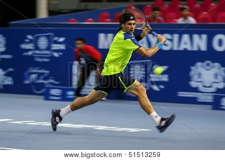 KUALA LUMPUR - SEPTEMBER 27: David Ferrer chases to hit a return to Joao Sousa in a quarter-final match of the Malaysia Open 2013 tennis played at the Putra Stadium, Malaysia on September 27, 2013.