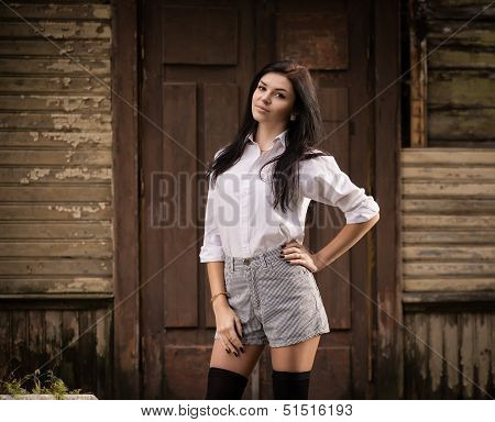 Fashion Pretty Young Woman Posing Outdoor Near A Old Wooden Wall.
