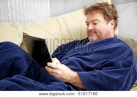 Scruffy looking unemployed man sitting home in his bathrobe using his tablet PC.