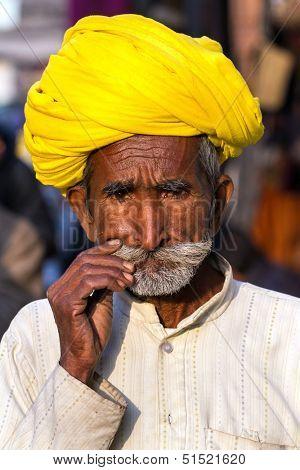PUSHKAR, INDIA - DECEMBER 1: A Rajasthani man wearing traditional colorful turban posing after Pushkar Camel Fair on December 1, 2012 in Pushkar, Rajasthan, India.