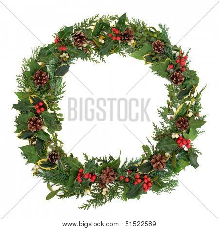 Natural christmas wreath with holly, mistletoe, ivy, pine cones and cedar leaf sprigs over white background.