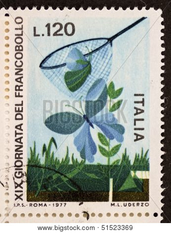 ITALY - CIRCA 1977: a stamp printed in Italy celebrates 19th Postage Stamp day showing butterflies on the grass and butterfly net. Italy, circa 1977