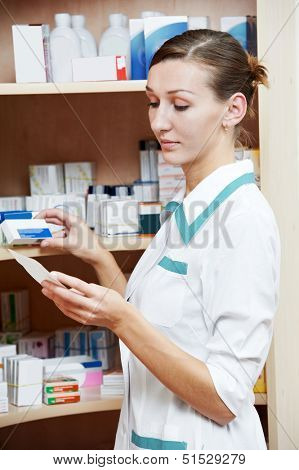 pharmacist chemist woman searching drugs in pharmacy drugstore warehouse