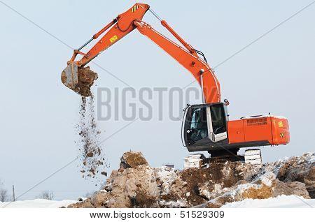 Heavy excavator loader at winter moving frozen soil works in sandpit