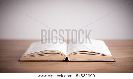 Open book on wooden table with empty space