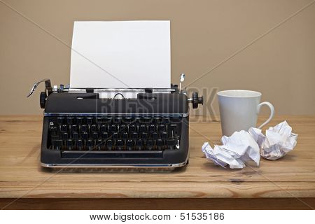 An old retro typewriter with a piece of blank paper for you to add your own text, coffee mug and two pieces of screwed up paper besides it on the desk.