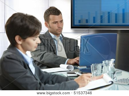 Businesspeople sitting around table at meetingroom, working.