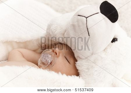 Closeup photo of beautiful baby with dummy and big bear hat.