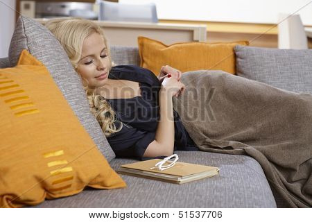 Attractive young woman lying on sofa, sleeping.