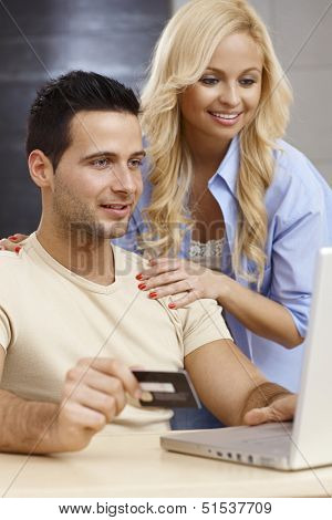 Young couple using laptop computer at home, shopping online, smiling happy.