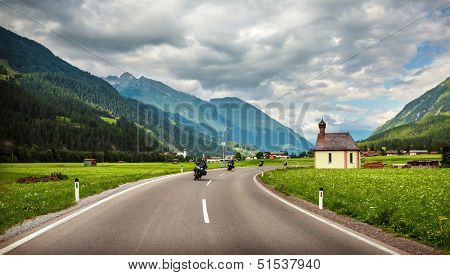 Bikers on mountainous highway, Europe, Austria, Alps, road along little village, driving motorcycle, extreme sport, active lifestyle concept