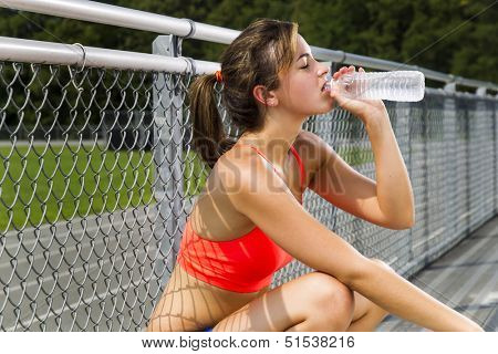 An athletic teenager relaxing after exercising on a track outdoors