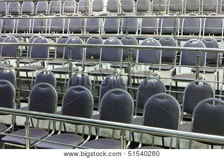 Rows of simple chairs with handrails in modern hall for business meetings.