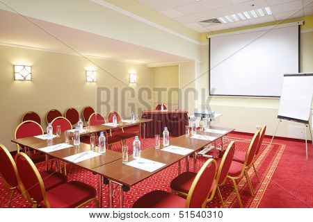 Projector, red chairs and tables in room with red carpet for business meetings.