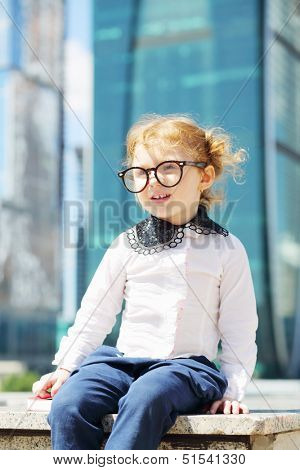 Little cute girl in glasses sits on border near skys?raper at sunny day.