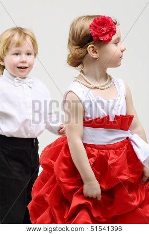Little boy admiringly looks at beautiful girl in red and white dress on grey background.