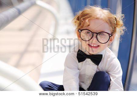 Little cute red hair girl in glasses sits on floor in gallery near window.