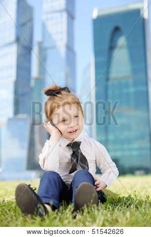 Little happy girl on grass talks by cell phone near skys?rapers at sunny day.
