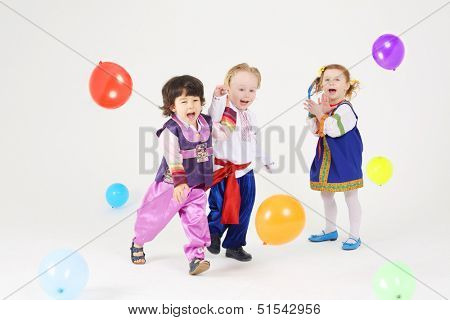 Little girl and two boys in folk costumes play with balloons on white background.