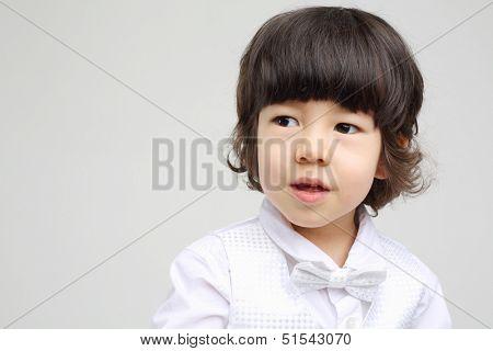 Little cute boy in white bow-tie looks away on grey background.