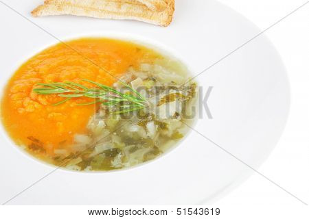 european cuisine: dual components vegetable soup with toasts isolated on white