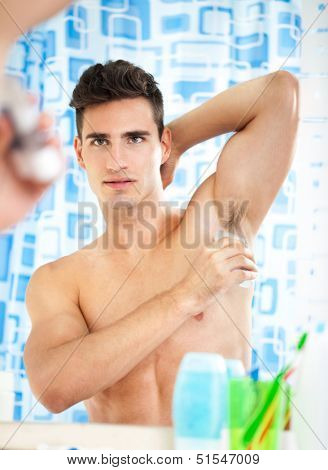 young handsome man applying antiperspirant and looks at himself in mirror