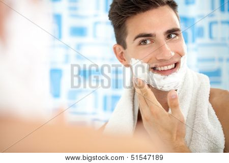 man shaving his face getting ready for the day