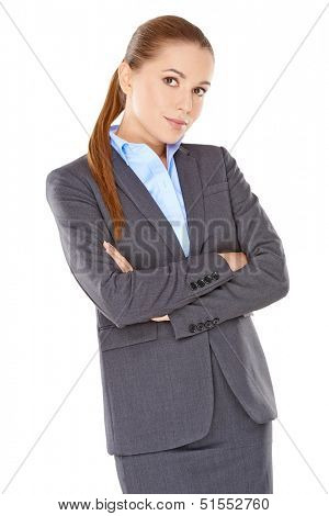 Sceptical businesswoman standing looking at the camera with her arms folded and a confident searching look  isolated on white