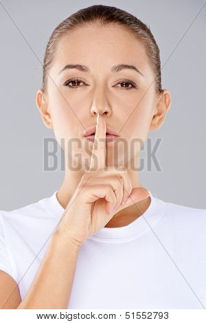 Woman making a shushing gesture with her finger raised to her lips as she requests silence or asks you to keep her secret