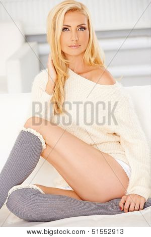 The lady with a blonde hair is wearing a sweatshirt and a gray knee high socks