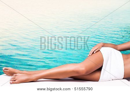 perfect woman legs light blue water in background