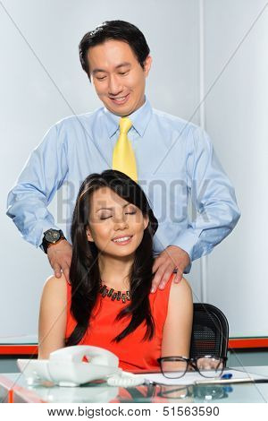 business woman or secretary having a massage and an office affair or relationship with her boss or colleague in office
