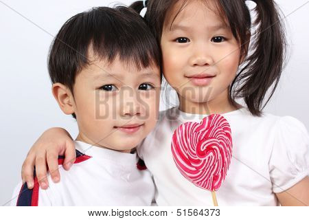 Cute boy and girl with lollipop